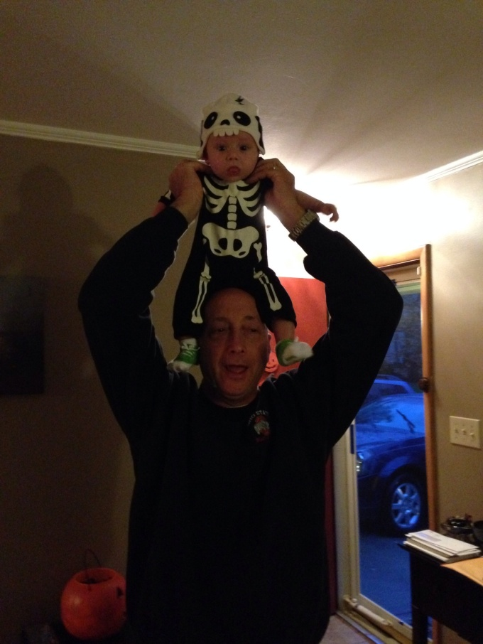 my husband putting my grandson on his head, and holding him.
